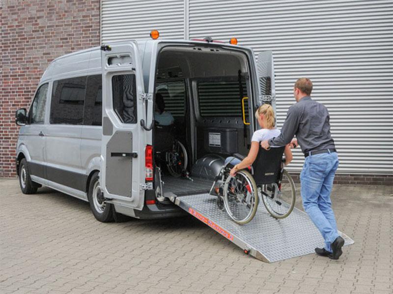 Wprowadzanie wózka inwalidzkiego z osoba niepłnosprawną po rampie aluminiowej do busa
